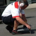 Механик Bridgestone измеряет температуру асфальта